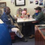 Lou Tyson and Colt sit at a booth in the Route 66 Museum